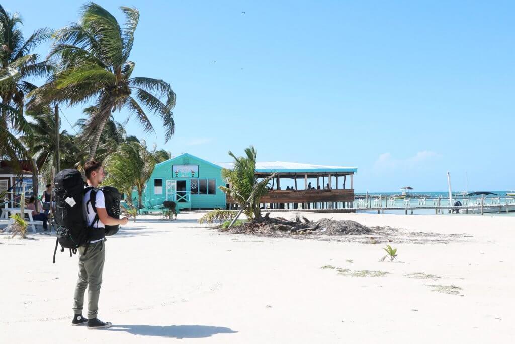 Daniel steht am Strand und wartet auf das Wassertaxi zur Insel Caye Caulker.