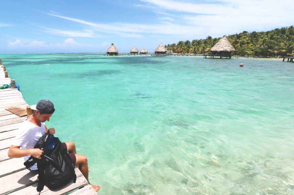 Daniel auf einem Steg der Insel Laughing Bird Caye vor der Küste von Belize. Vor ihm: glasklares Wasser.