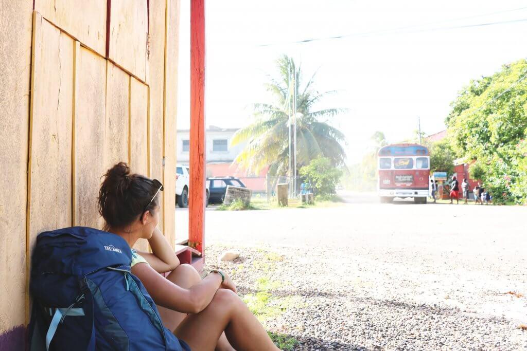 Ania sitzt neben ihrem Rucksack auf dem Boden und genießt das stressfreie Leben in Belize.