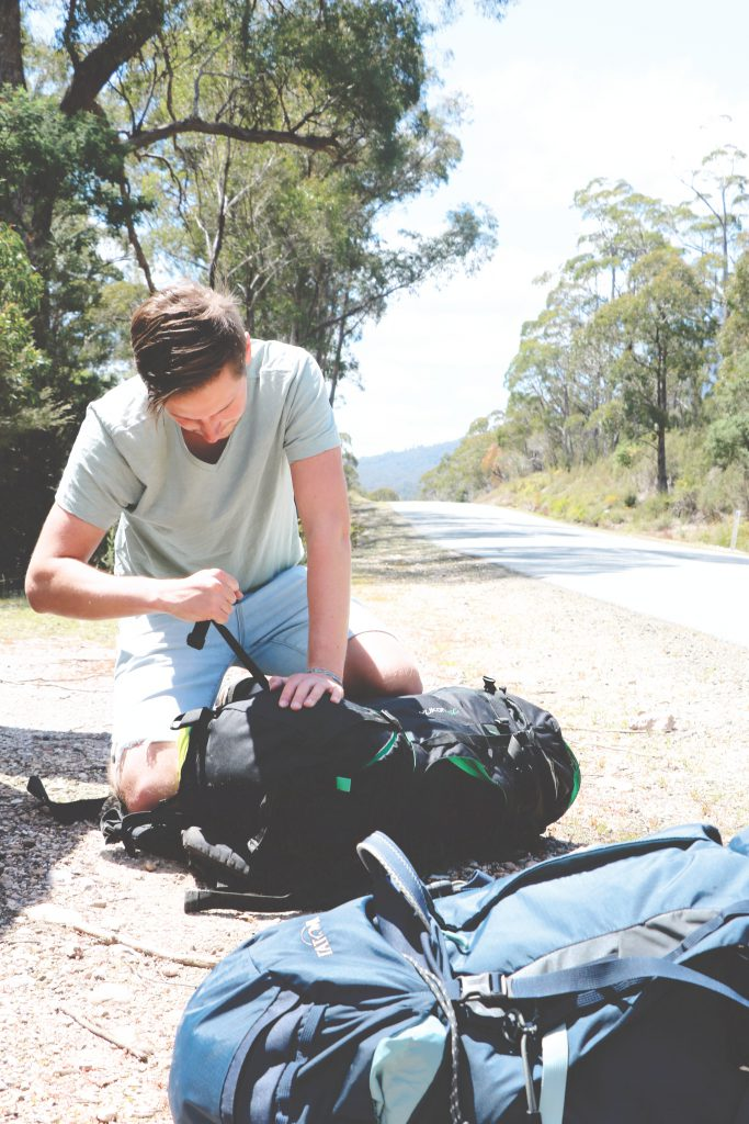 Daniel kniet am Straßenrand vor dem Nationalpark auf Tasmanien und packt seinen Tatonka Yukon Trekkingrucksack.