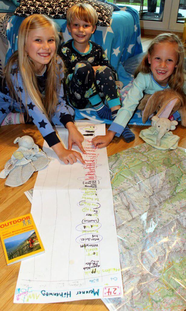Die drei Kinder schauen sich die geplante Tour auf der Karte an