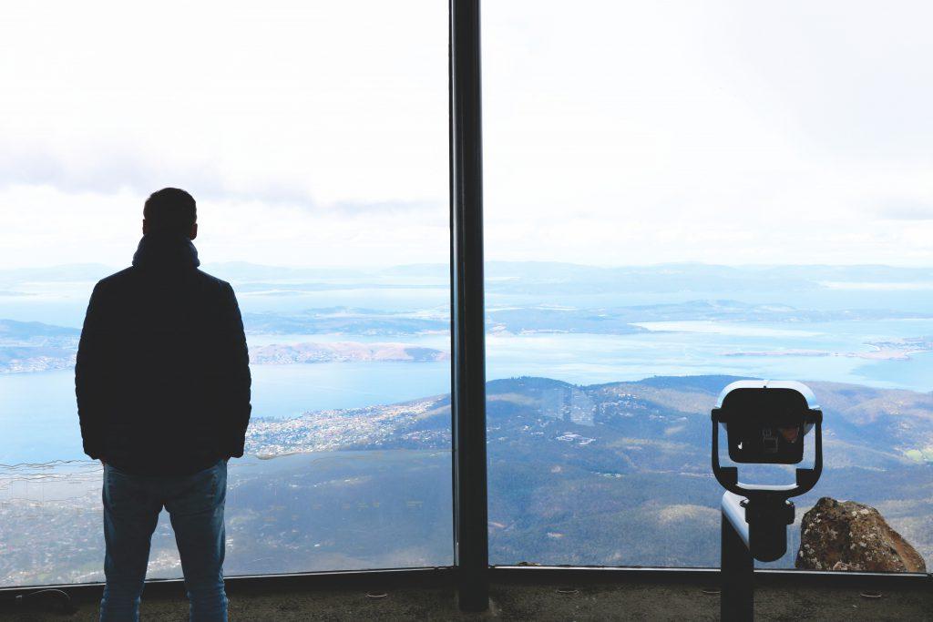 Auf dem Gipfel des Cradle Mountain: Daniel schaut mit einem Rundumblick auf die unten liegenden Seen und Wanderwege des Cradle-Mountain-Lake-St.-Clair-Nationalparks auf Tasmanien.