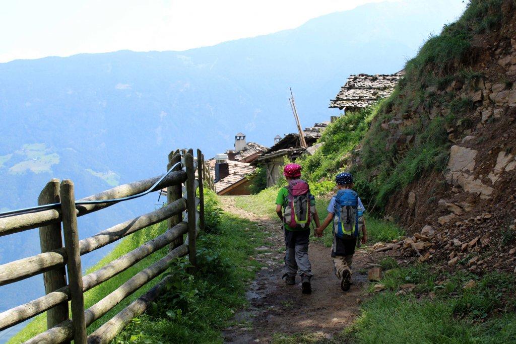 Die Kinder wandern Hand in Hand den Meraner Höhenweg entlang.
