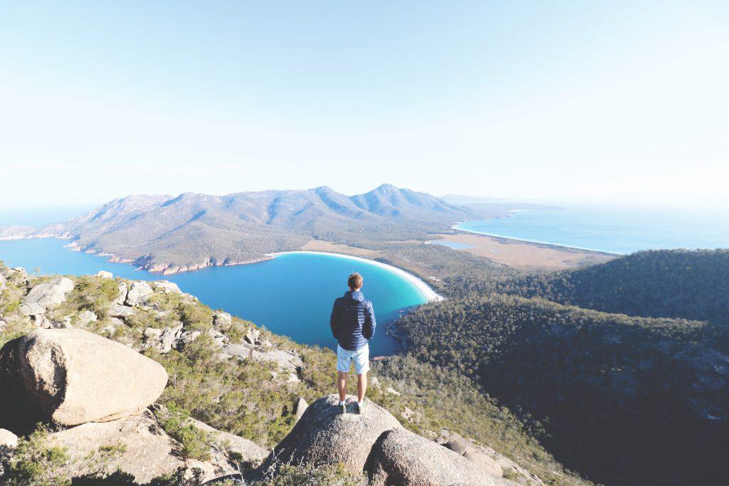 Daniel blickt von einem Berg im Freycinet Nationalpark auf die für Tasmanien berühmte Wineglass Bay Bucht.