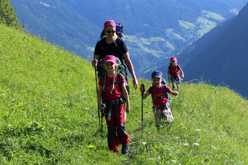 Die Familie wandert über eine grüne Wiese.