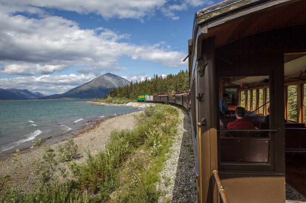 Die Eisenbahn fährt am Ufer eines Sees entlang.