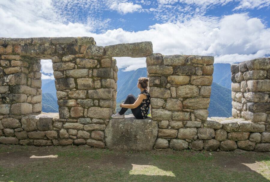 Melanie Schillinger sitzt auf einer Mauer der Winay Wayna Ruine in Peru.