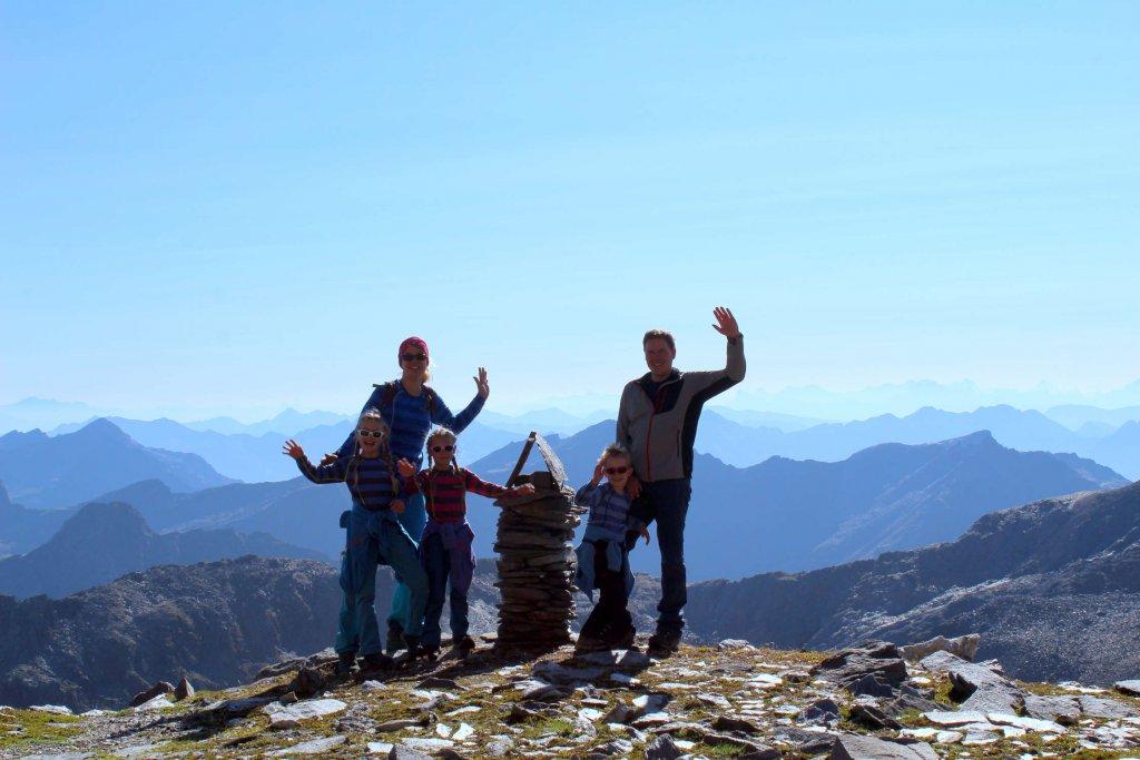 Die Familie posiert für ein Gruppenfoto neben einem Steinmandl.