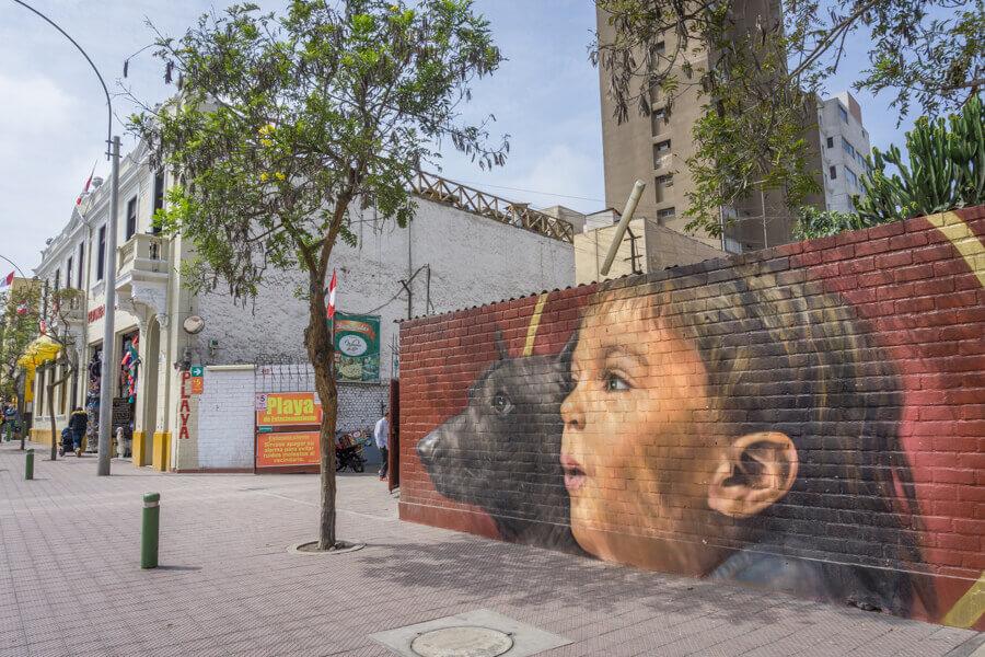 Street-Art an einer Mauer in Perus Hauptstadt Lima. Zu sehen sind die Gesichter eines Kindes und eines Hundes.