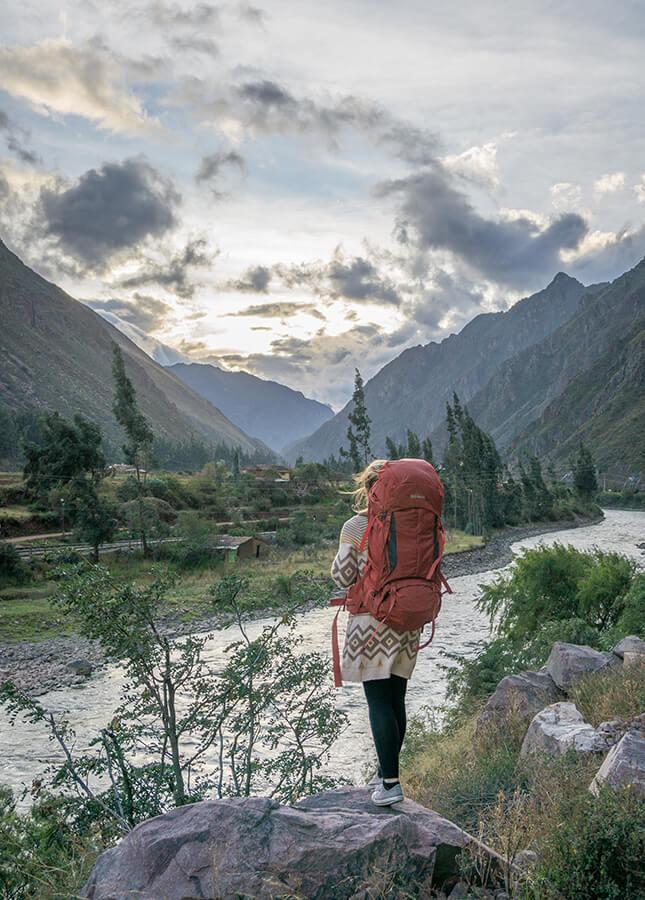 Melanie Schillinger mit ihrem Yukon Trekkingrucksack vor einem Fluss nahe Machu Picchu in Peru.
