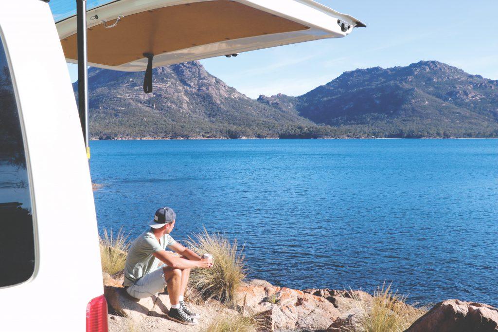 Meerblick: Daniel genießt eine Tasse Kaffee direkt am Meer. Links neben ihm der Van mit die beiden durch Tasmanien fuhren.