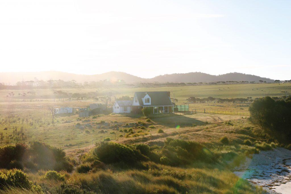 Ein einsames Haus entlang der Felder von Tasmanien. Kein seltener Anblick für Ania und Daniel während ihres Roadtrips über die kleine australische Insel.