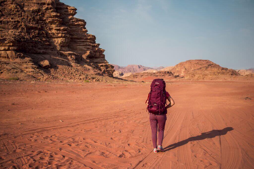 Maria mit ihrem Tatonka Yukon Trekkingrucksack in der Wüste Wadi Rum mit Blick auf die umliegenden Felsen.