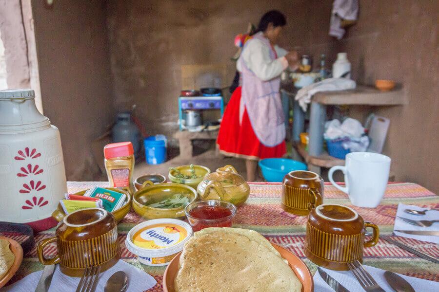 Quechua-Frau beim Zubereiten von Speisen in einem Homestay am Titicacasee.
