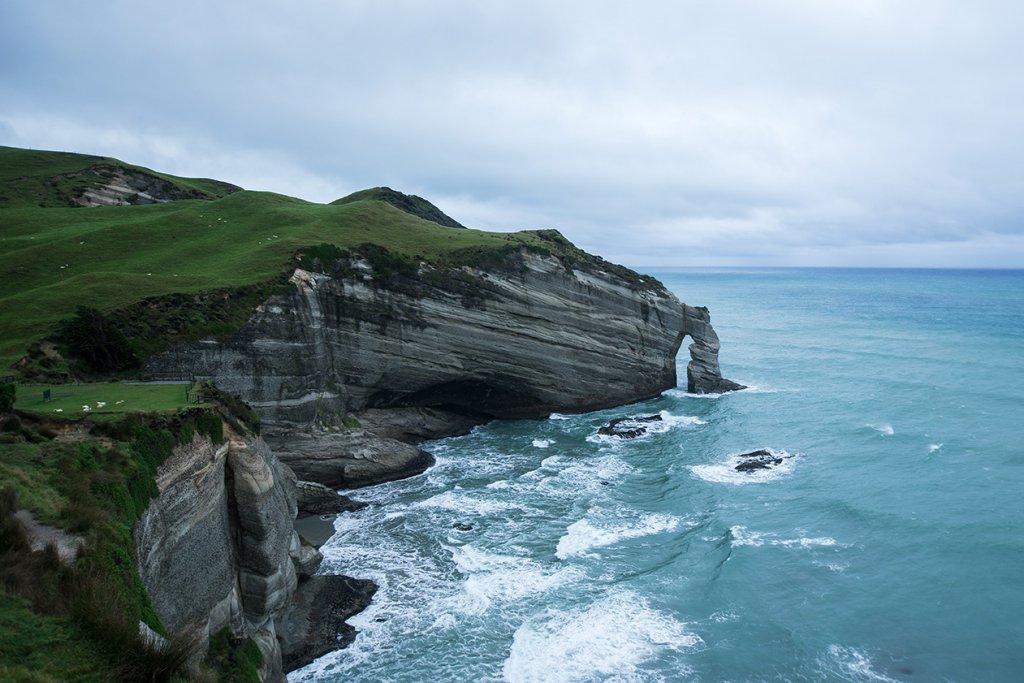Steile Felsen an der Küste des Wharariki Beach im Norden von Neuseeland.