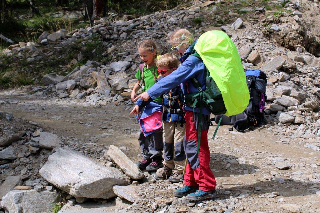 Die Kinder lachen und zeigen auf etwas am Weg.