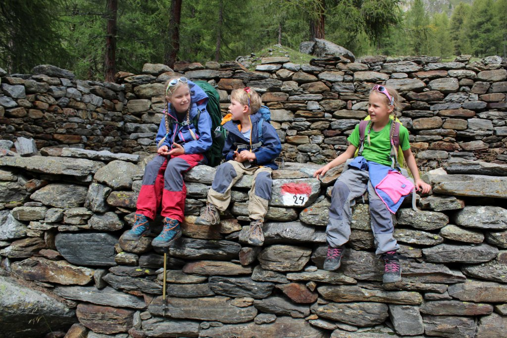 Die Kinder sitzen auf einer Mauer und legen eine kurze Pause ein.