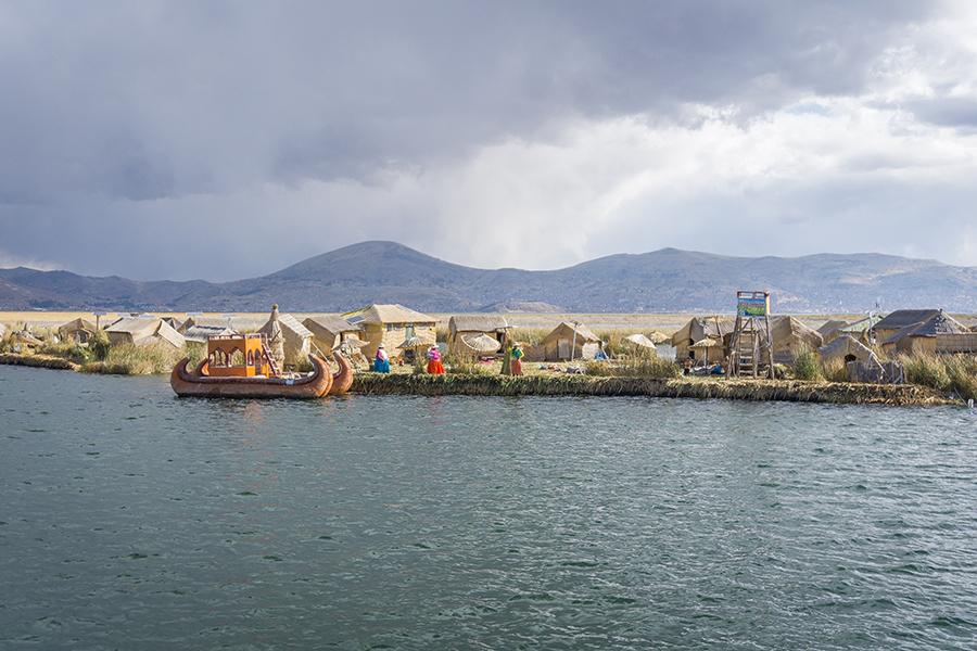 Boote und Hütten am Ufer von Puno.