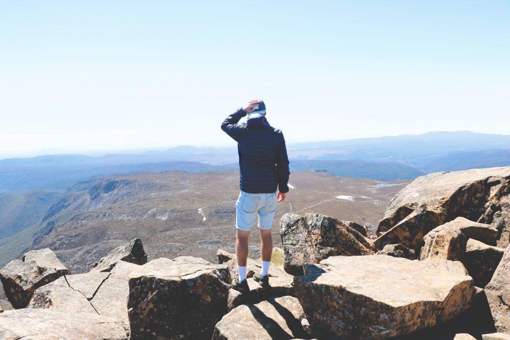 Daniel blickt auf einem Berg stehend auf die umliegende Gebirgslandschaft Tasmaniens.