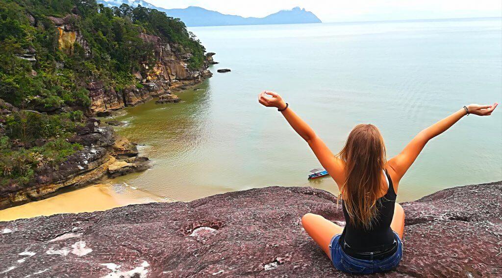 Sarah blickt von einem Aussichtspunkt auf eine Bucht im Bako Nationalpark auf Borneo.