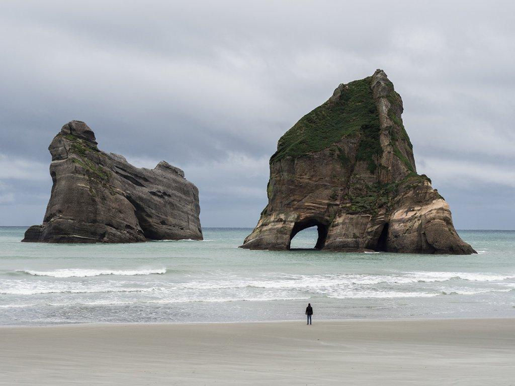 Riesige Felsen ragen am Wharariki Beach in Neuseeland aus dem Wasser.