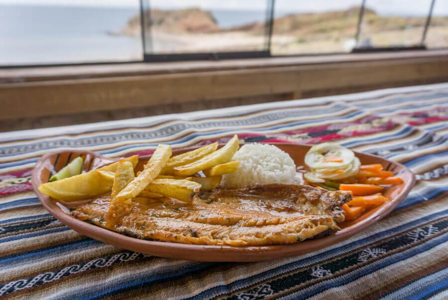 Spezialität am Titicacasee - Gegrillte Forelle, mit Reis, fruchtiger Limette und knusprigen Pommes serviert.