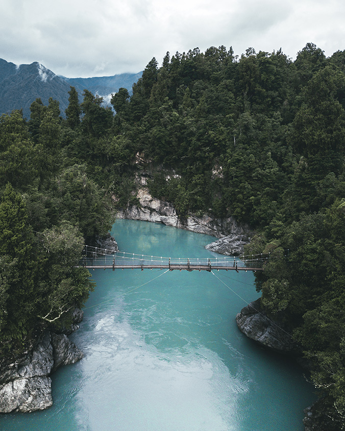 Roadtrip Neuseeland: Hängebrücke über dem Hokitika River mit seinem blau-grünen Wasser.