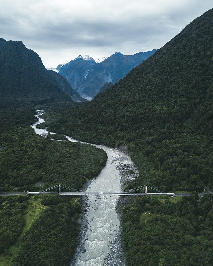 Drohnenaufnahme: Blick in Tal mit Fluss und Autobrücke auf der Fahrt nach Wanaka.