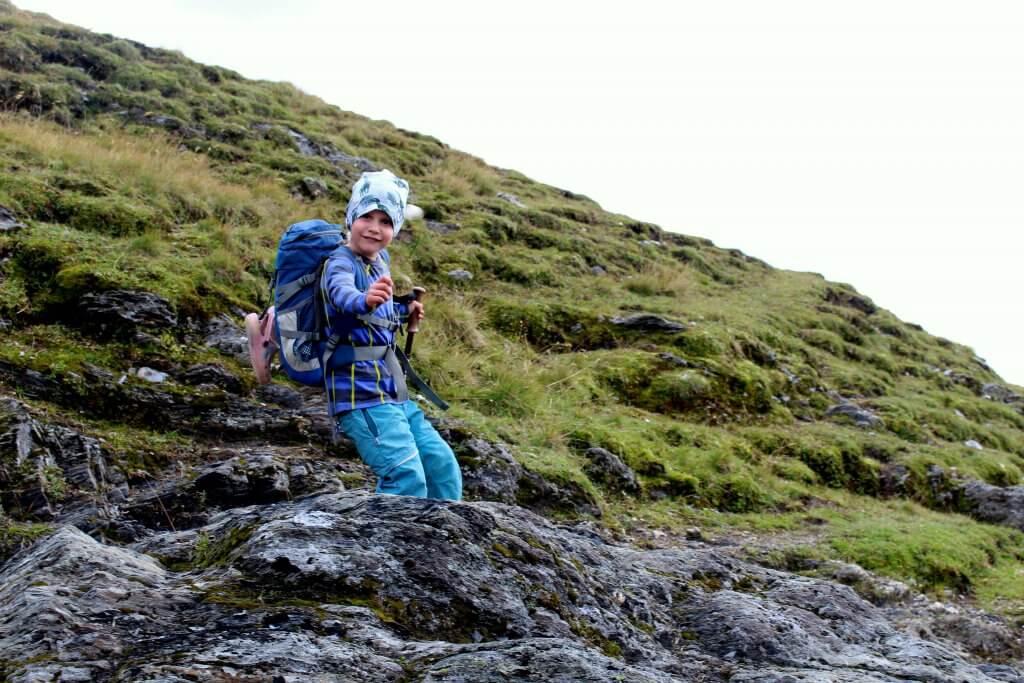 Frederik mit seinem Rucksack lachend auf einem Pfad des Weitwanderwegs Tour du Mont Blanc.