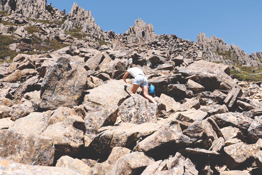 Ania zieht sich mit beiden Händen die Felsen im Cradle-Mountain-Lake-St.-Clair-Nationalpark hoch.