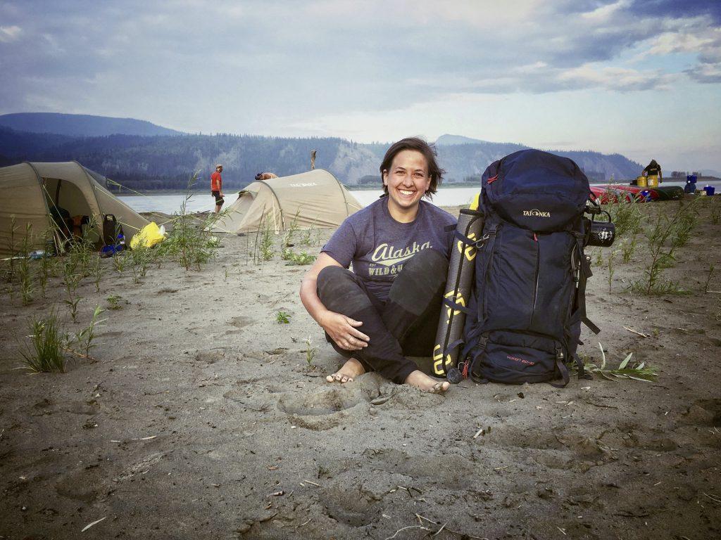 Yukon River Kanutour - Anna sitzt mit ihrem Yukon Trekkingrucksack am Campingplatz.