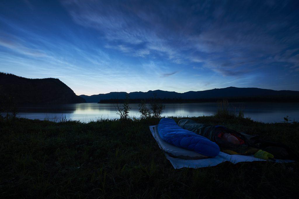 Yukon River Kanutour - Biwak-Nachtlager mit Schlafsack am Ufer des wilden Flusses.