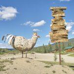Yukon River Kanutour - Große Huhn-Skulptur und Richtungs-Schilder.