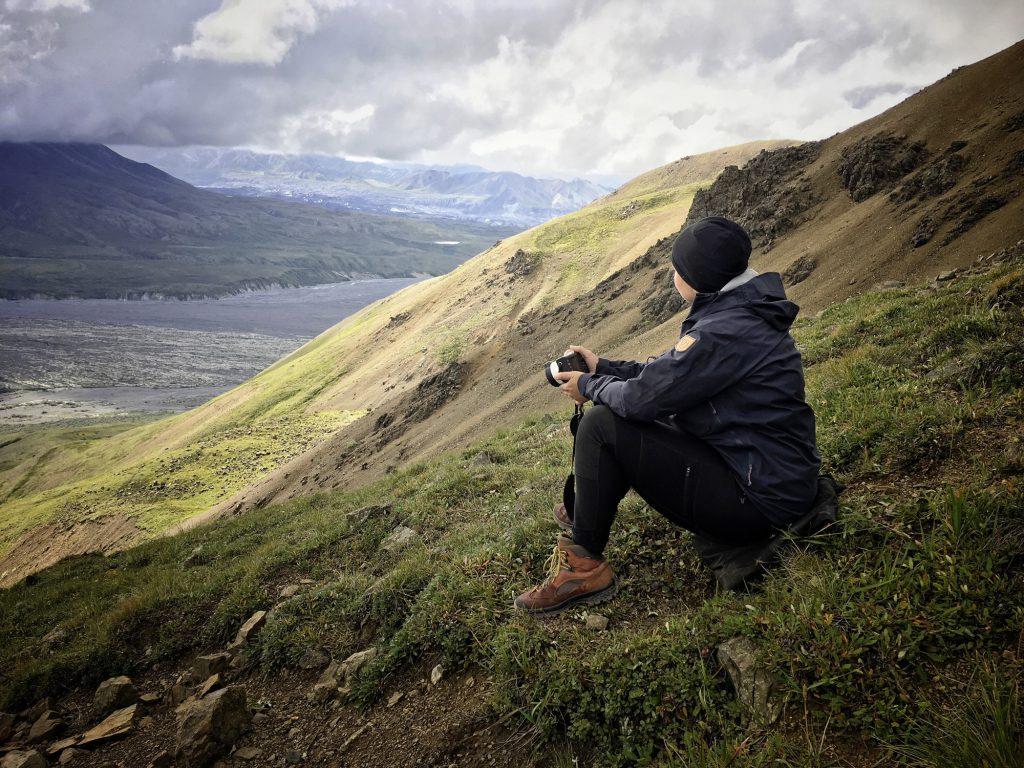 Yukon River Kanutour - Anna sitzt mit ihrer Fotokamera am Hang eines Hügels im Denali Nationalparks.