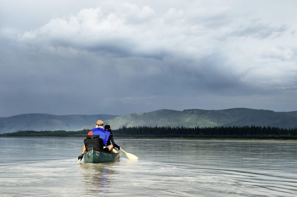 Yukon River Kanutour - Kanu auf dem wilden Fluss. Darueber: dunkle Regenwolken.