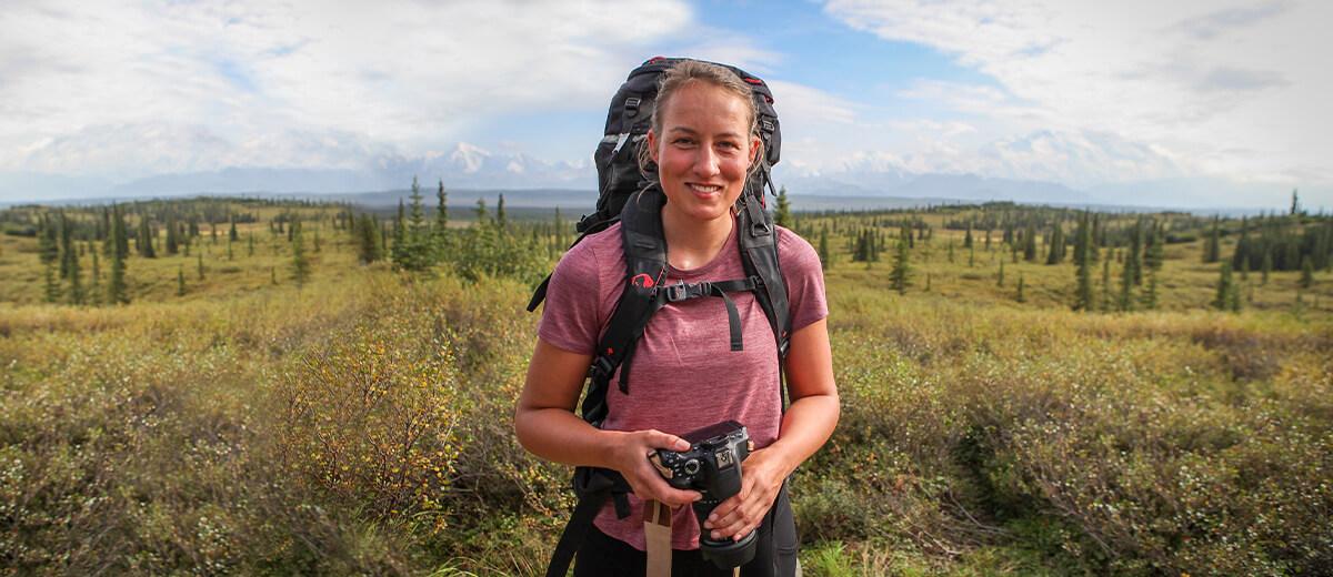 Melissa ausgestattet mit Tatonka Trekkingrucksack Yukon und Fotoapparat.