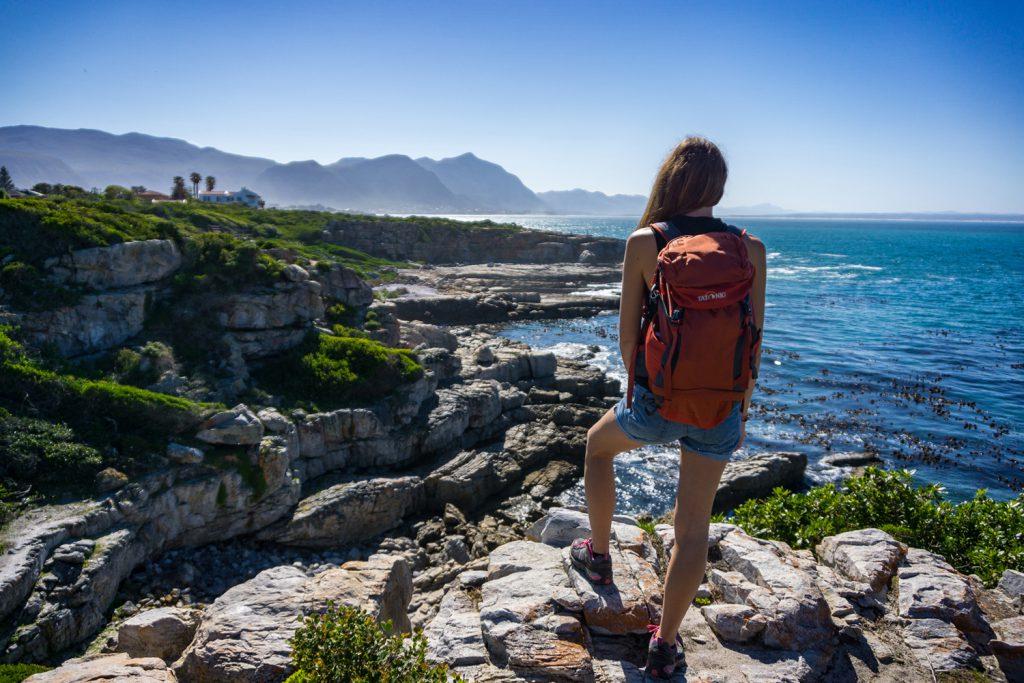 Garden Route Südafrika - Sara von blickt vom Cliff Path in Hermanus auf die vor ihr liegenden Berge und das Meer.