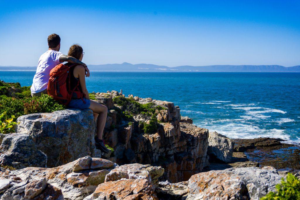 Garden Route Südafrika - Sara und Marco sitzen auf Felsen und blicken auf das Meer. In der Stadt Hermanus lassen sich sehr gut Wale beobachten.