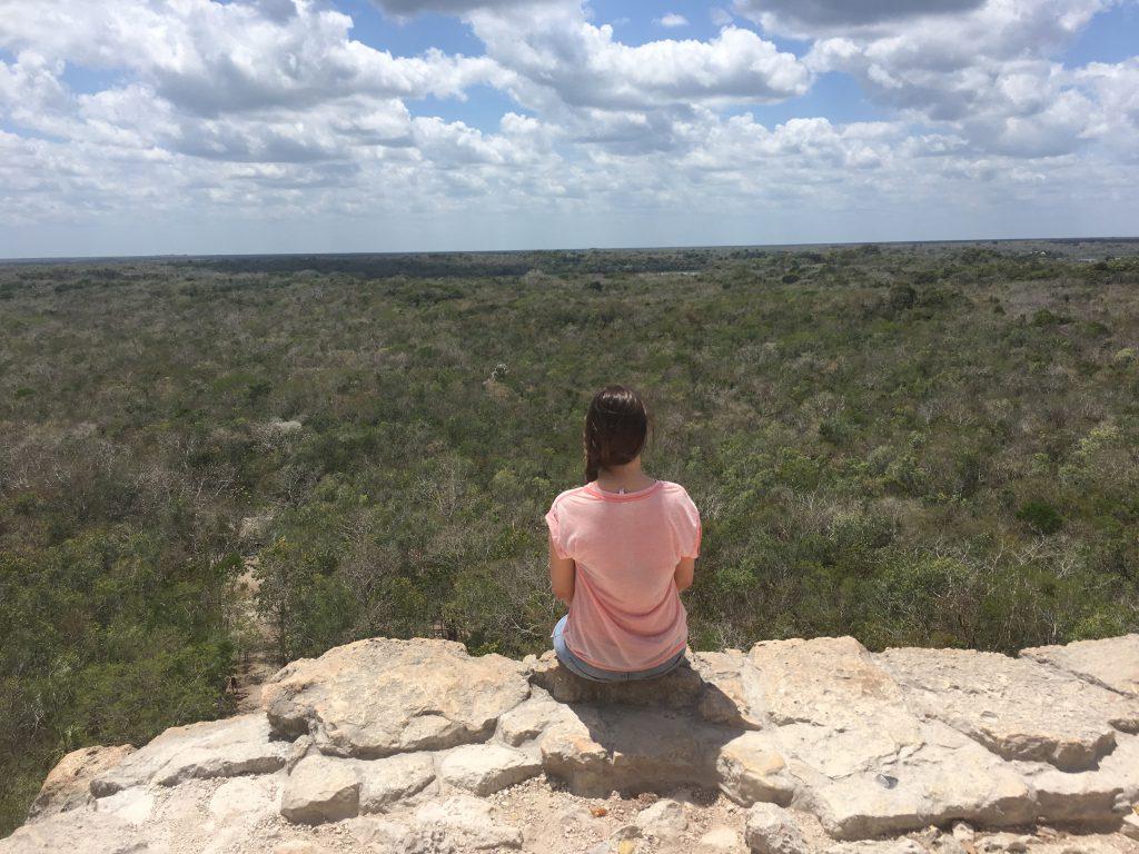 Roadtrip Yucatan - Sophie sitzt auf der Nohoch Mul Maya-Pyramide und blickt auf den umliegenden Dschungel der Ruinenstätte Coba in Mexiko.