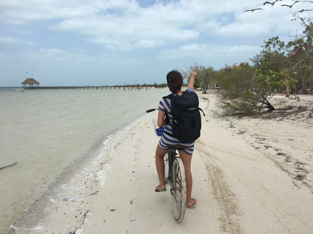Roadtrip Yucatan - Sophie fährt mit einem Fahrrad den Strand von Holbox entlang und zeigt mit ausgestrecktem Arm nach vorne.