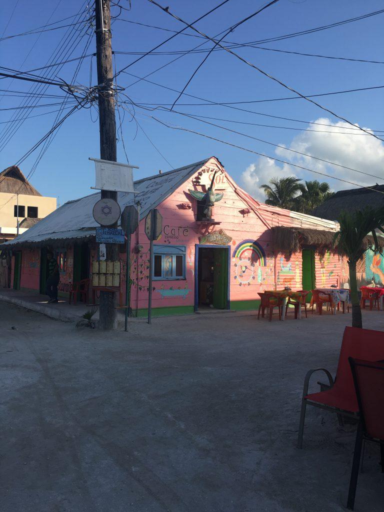 Roadtrip Yucatan - Kleines Cafe an einer Straßenecke in Holbox, Mexiko. Die wände sind mit rosa Farbe bemalt.