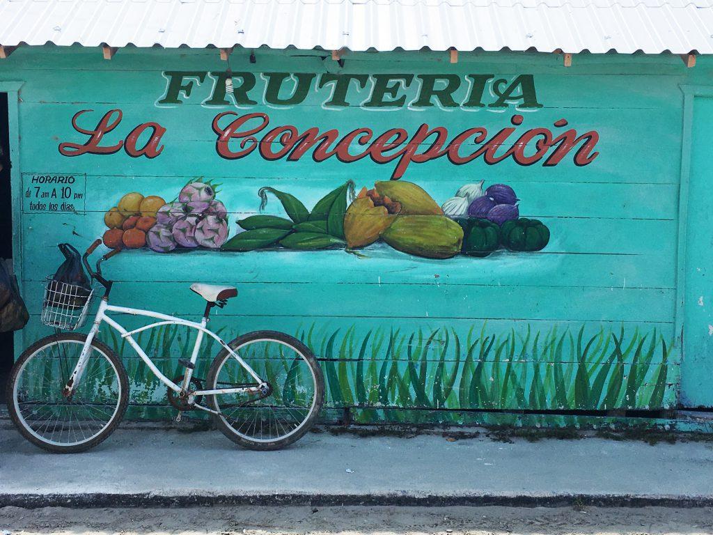 Roadtrip Yucatan - Fahrrad vor der handbemalten Wand eines Lebensmittelgeschäfts in Holbox, Mexiko.