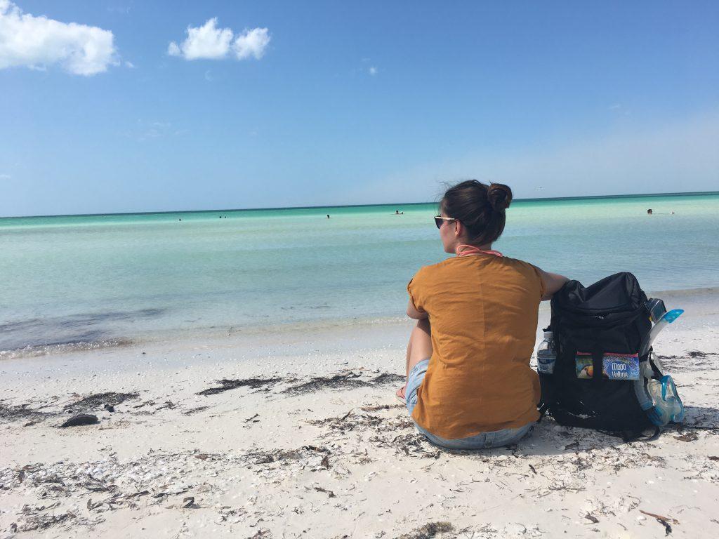 Roadtrip Yucatan - Sophie sitzt am Strand von Holbox in Mexiko und genießt das Rauschen des Meeres.