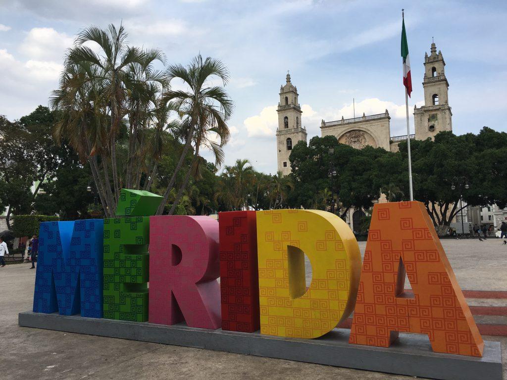 Roadtrip Yucatan - In bunten Großbuchstaben ist der Name der Stadt Mérida zu lesen. Im Hintergrund: die Catedral de San Idelfonso auf der Plaza de la Independencia.