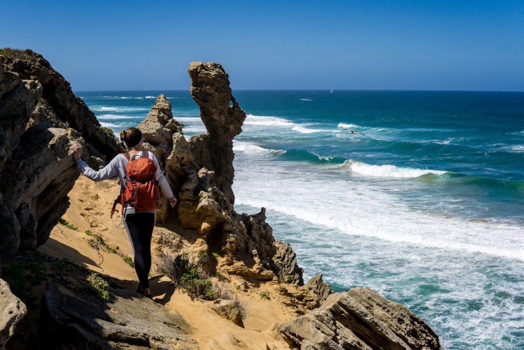 Die Garden Route Südafrika - Sara von der Tatonka Trekkin' Crew an einer Klippe am Meer vor Südafrika.
