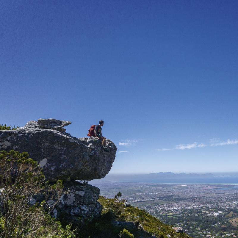 Garden Route Südafrika - Marco auf einem Felsvorsprung sitzend mit Blick auf Kapstadt.