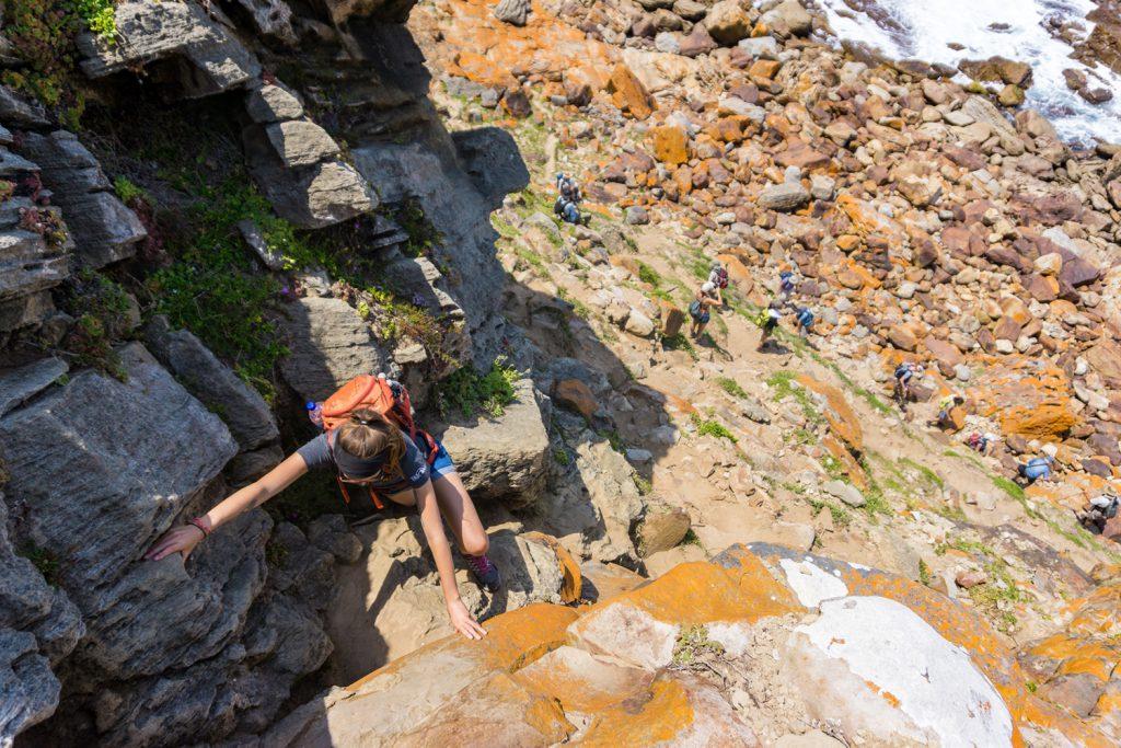 Garden Route Südafrika - Auf einem Trek des Robberg Nature Reserve in Plettenberg Bay, klettert Sara ein paar Felsen hinauf.
