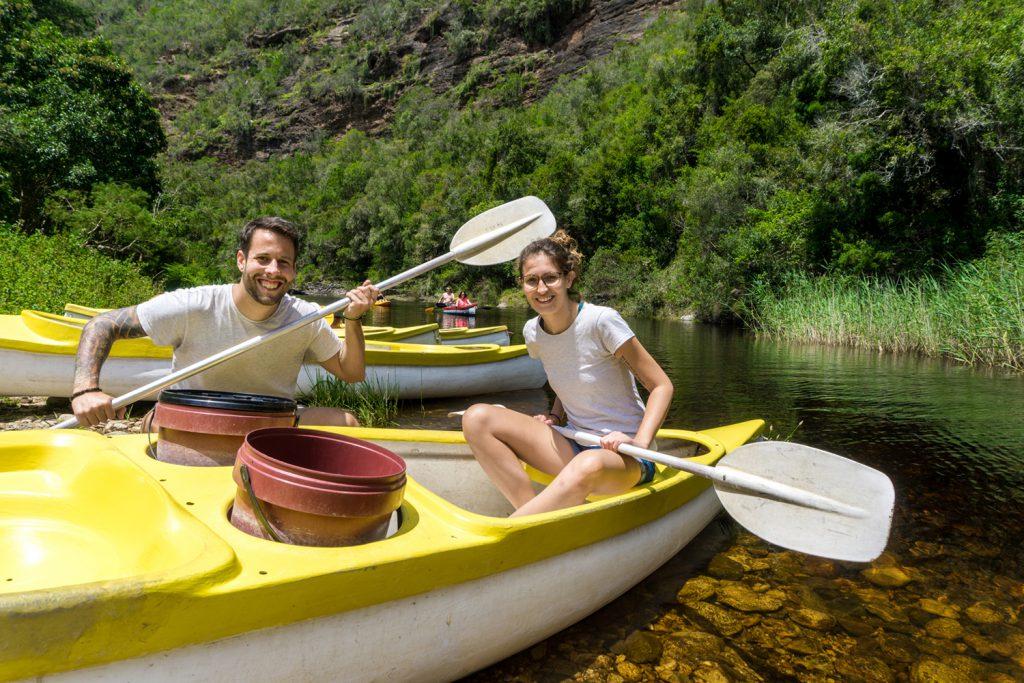 Garden Route Südafrika - Sara und Marco sitzen auf Fluss Touw in einem gelb-weissen Kanu.