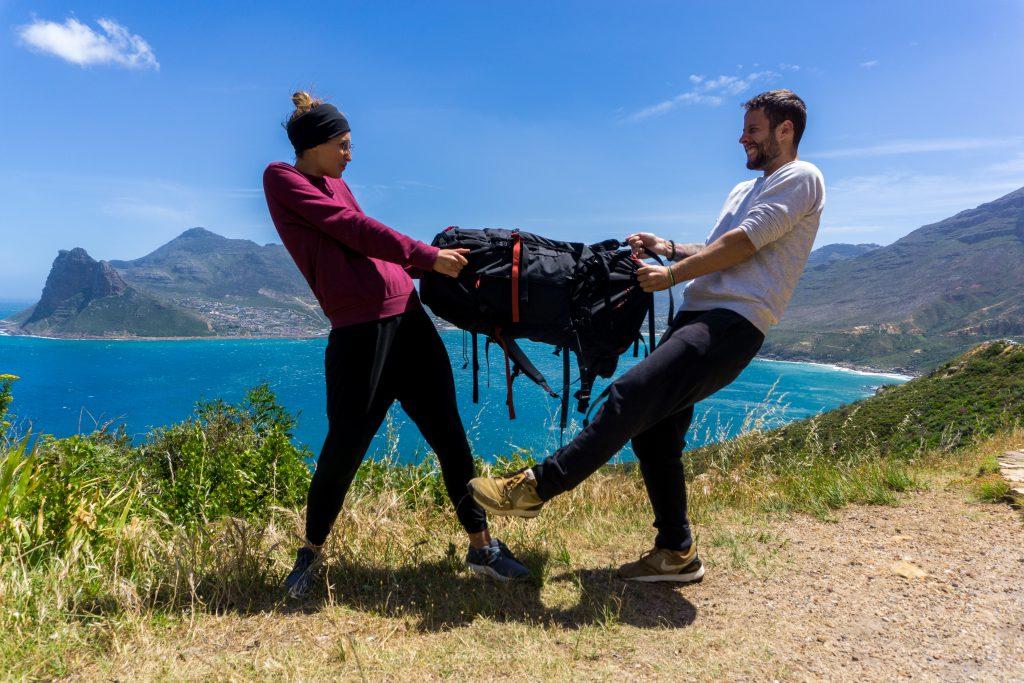 Garden Route Südafrika - Wer bekommt den Tatonka Yukon? Sara und Marco zerren beide um den Trekkingrucksack. Aber keine Sorge: Alles nur Spaß.