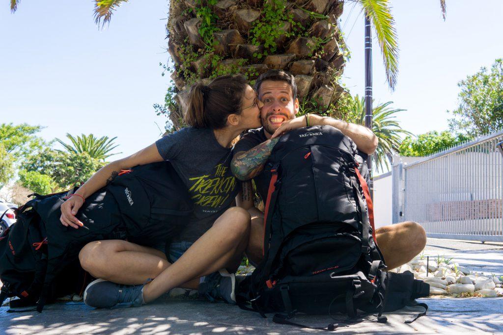 Garden Route Südafrika - Sara und Marco von der Tatonka Trekkin' Crew sitzen vor einer Palme. Im Arm haben sie ihre beiden Tatonka Yukon Trekkingrucksäcke.